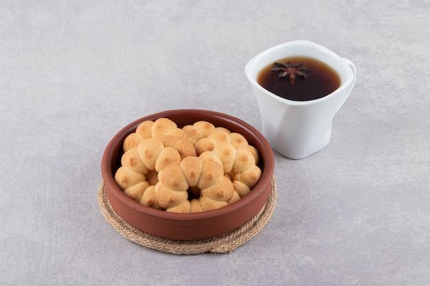 Tonschale mit süßen keksen und einer tasse tee auf dem tisch.