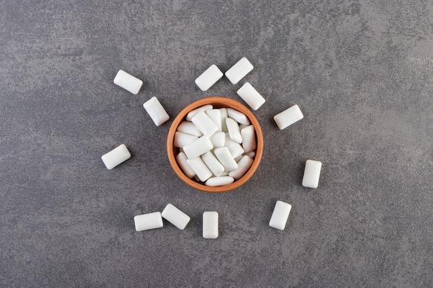 Tonschale voller weißer kaugummis auf einem steintisch.