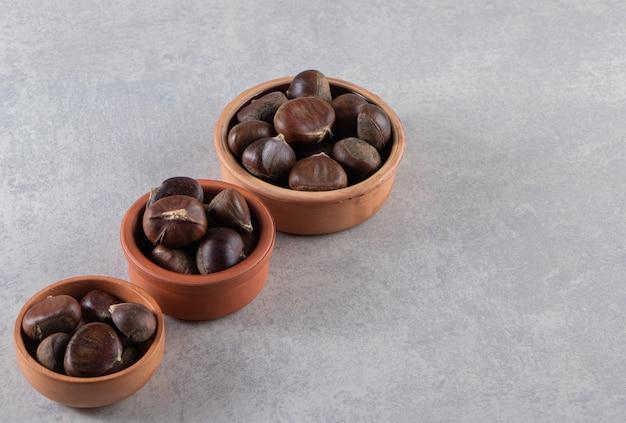 Tonschalen mit organischen geschälten kastanien auf steintisch.