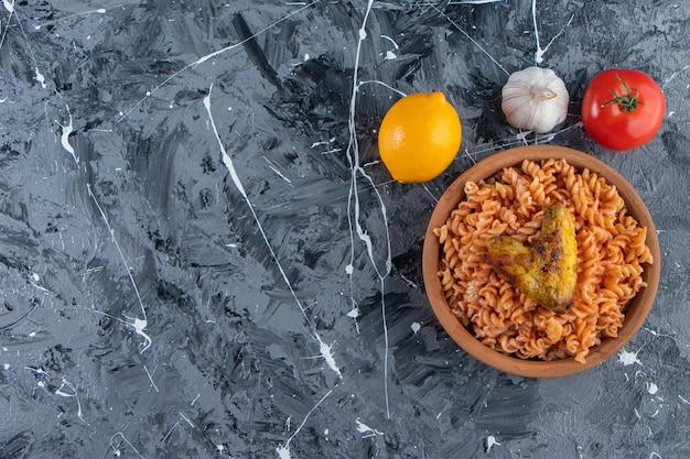 Tonschüssel mit köstlichen fusilli-nudeln mit gebratenem flügel auf marmorhintergrund.