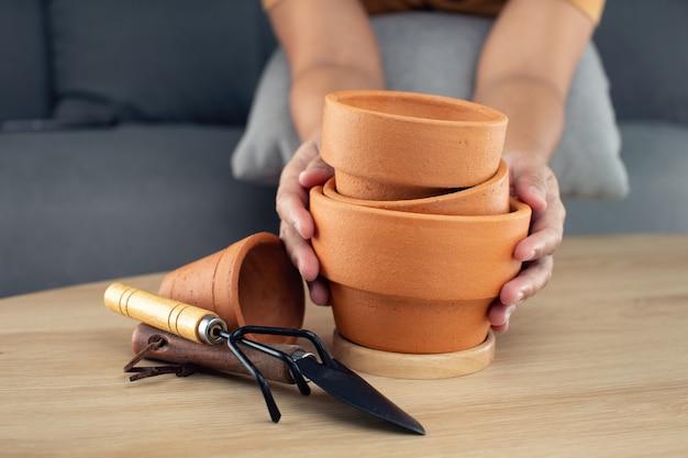 Tontöpfe und accessoires auf holztischen. vorbereiten der werkzeuge und geräte vor dem pflanzen