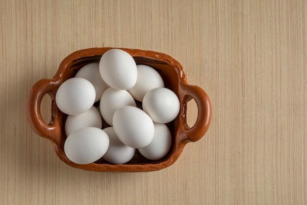 Tontopf gefüllt mit weißen eiern auf holzunterlage mit werbefläche oben