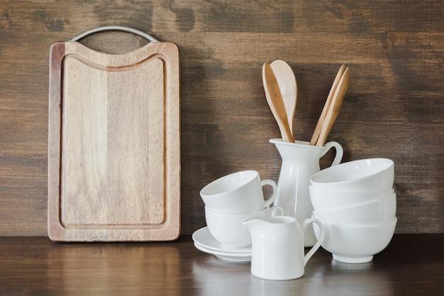Tonware, weiße geräte und anderes unterschiedliches material auf hölzerner tischplatte