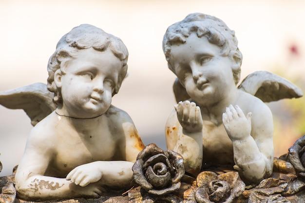 Tonwarenskulptur des engels mit zwei babys mit einer metallischen rose