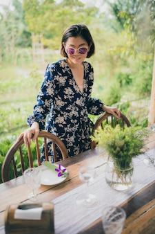 Toothy lächelndes gesicht der schönen asiatischen frau mit entspannendem gefühl neben lebensmitteltabelle