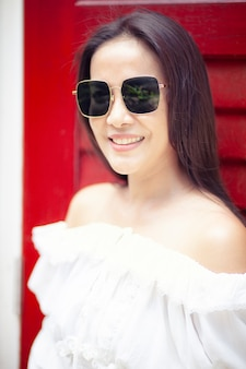 Toothy lächelndes gesicht der schönen asiatischen tragenden sonnenbrille der jüngeren frau