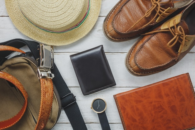 Top-ansicht-accessoires, um mit mann-kleidung-konzept zu reisen. brieftasche auf hölzernen background.watch, tasche, hut, notebook und schuh auf weißem holz tisch.