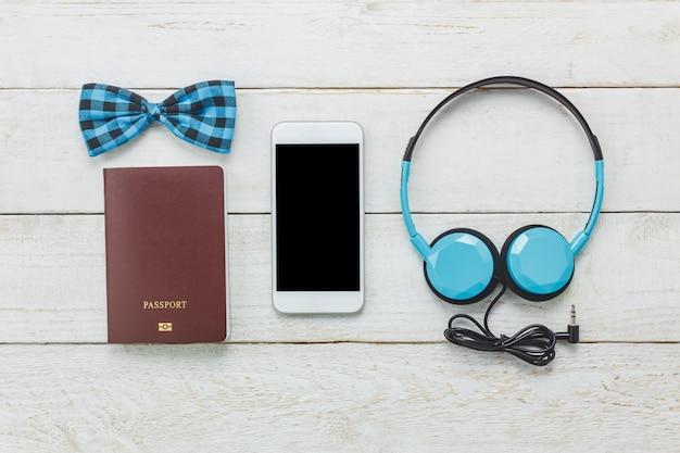 Top-ansicht-accessoires, um mit mann-kleidung-konzept zu reisen. fliege, pass auf holzuntergrund. kopfhörer auf holztisch.