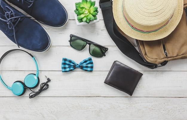 Top-ansicht-accessoires, um mit mann-kleidung-konzept zu reisen. kopfhörer auf hölzernen background.bow krawatte, brieftasche, sonnenbrille, schuh, tasche und hut auf holz tisch.