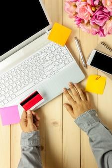 Top-ansicht business-office-konzept business-person halten kreditkarte mit laptop und handy, notebook, blume auf schreibtisch.