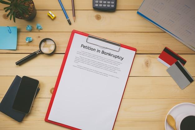 Top-ansicht business-office-konzept geschäft diskutieren petition in konkurs form, kreditkarte, handy, kaffee, kalender auf büro-schreibtisch.
