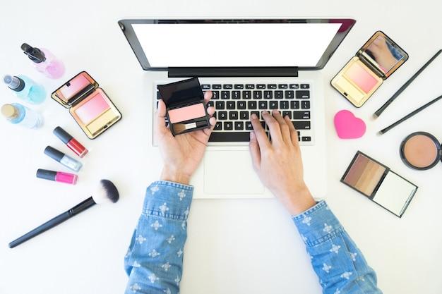 Top-ansicht der frauen mit laptop für die suche kosmetische informationen für make-up, beauty-konzept.