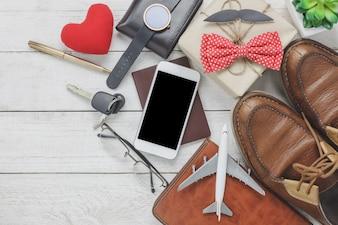 Top-Ansicht Happy Father Tag mit Reise-Konzept.Mobile Telefon und Pass auf rustikalen hölzernen Hintergrund. Zubehör mit Flugzeug, Schnurrbart, Vintage-Fliege, Stift, Geschenk, weißer Schlüssel Auto, Schuhe und Notebook, Baum.