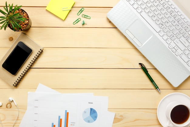 Top-ansicht laptop-notizbuch, stift, schwarzer kaffee, gezeichnetes papier, stationär, kopfhörer, gezeichnetes papier auf bürotischhintergrund.