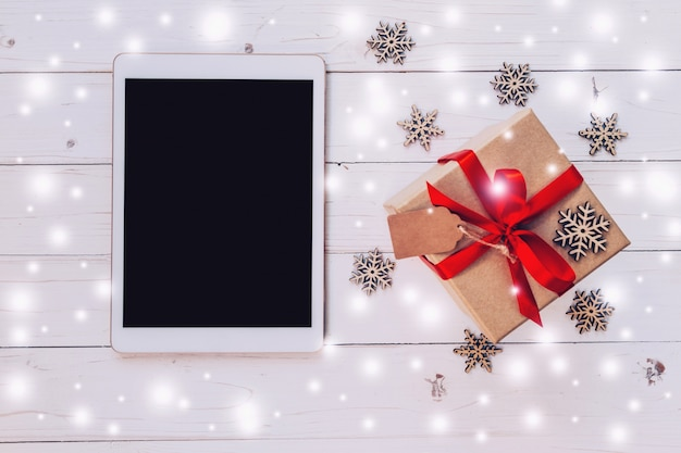 Top-ansicht tablette und geschenk-box mit schnee, schneeflocken auf weißem holz hintergrund für weihnachten und neujahr.