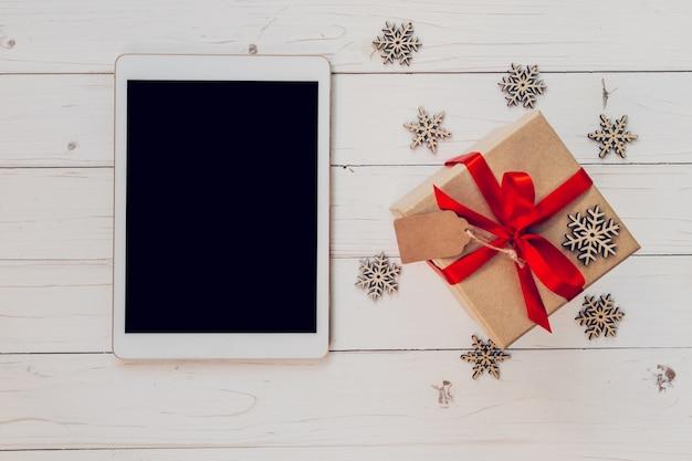 Top-ansicht tablette und geschenk-box mit schneeflocken auf weißem holz hintergrund für weihnachten und neujahr. weihnachten und neujahrskonzept.