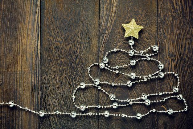 Top-ansicht weihnachten background.fir baum von weihnachten dekorationen, weihnachten gold stern und schmuck wäscheleine auf holztisch hintergrund mit kopie raum.