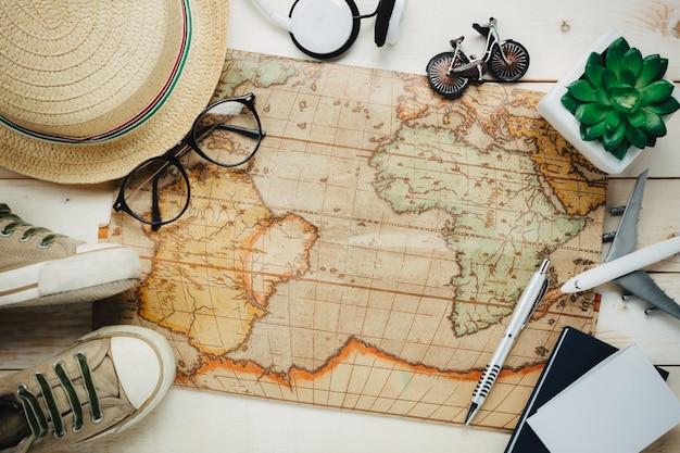 Top ansicht wesentliche reise items.the taschenrechner tasche notebook baum karte pass flugzeug kopfhörer musik brillen auf weißem holz hintergrund.