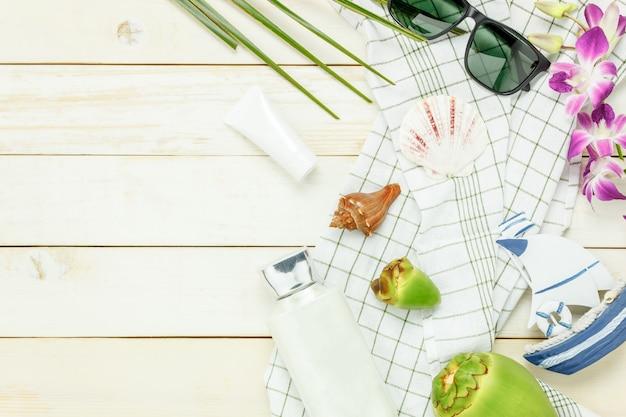 Top-ansicht wesentliche reise sommer artikel.die sonnencreme kokosnuss hut sonnenbrille auf weißem holz hintergrund.
