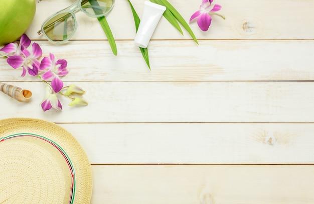 Top-ansicht wesentliche reise sommer items.the sonnencreme feuchtigkeitsspendende hut sonnenbrille orchidee auf weißem holz hintergrund.