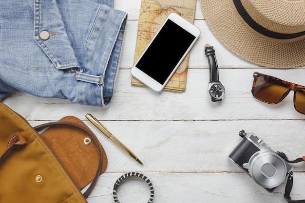 Top-ansicht zubehör, um mit frauen kleidung konzept zu reisen. weißer handy, uhr, tasche, hut, karte, kamera, halskette, hose und sonnenbrille auf weißem holz tisch.