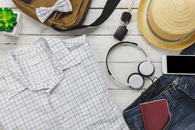 Top-ansicht zubehör, um mit mann kleidung konzept.white hemd, jeans, handy hören musik von kopfhörer auf hölzernen background.bag, pass, schlüssel, sonnenbrille und hut auf holz tisch.