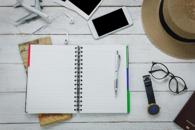 Top-ansicht zubehör zu reise-konzept.notebook freien platz für das schreiben mit stift auf weißen tisch backgroun.items ist karte, uhr, brillen, pass, hut, handy, flugzeug, auge, foto.