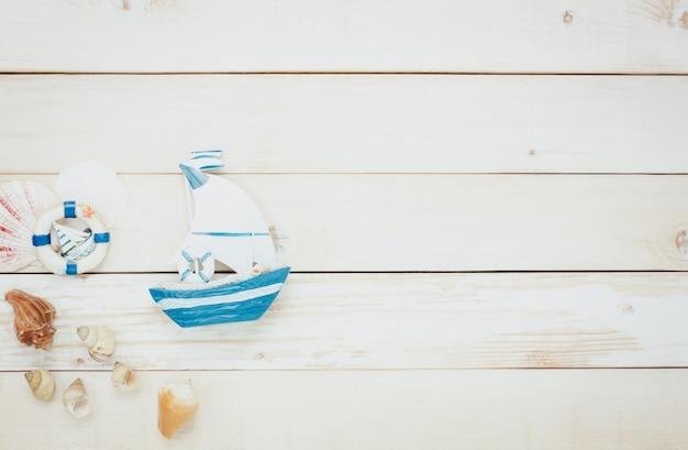 Top-ansicht zubehör zu reisen beach.vintage segelboot mit shell auf holzuntergrund.