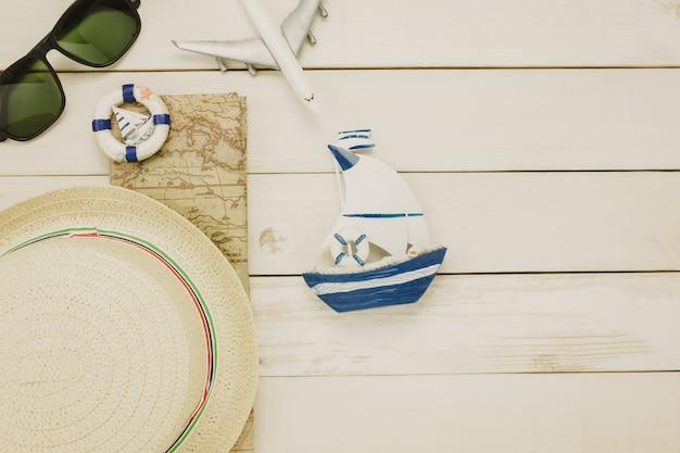 Top-ansicht zubehör zu reisen beach.vintage segelboot mit shell-fahrrad auf holzuntergrund.