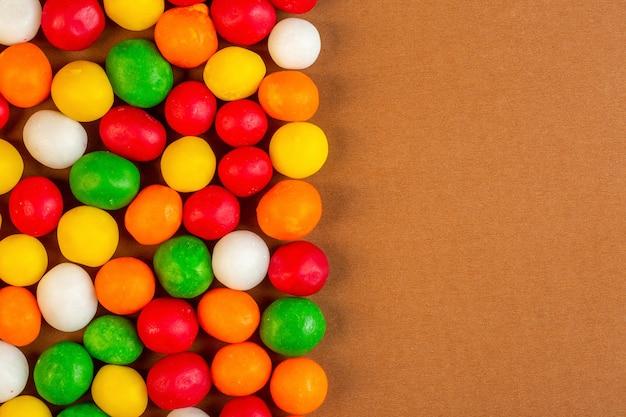 Top bunte bonbons mit kopienplatz auf ocker