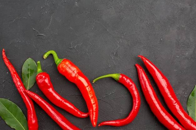 Top close view rote paprika und pay leaves auf schwarzem tisch mit kopierraum