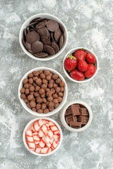 Top close view schalen mit süßigkeiten erdbeeren pralinen müsli und kakao auf dem grau-weißen boden mit freiem platz