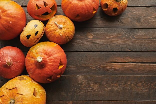 Top-down flach lag schuss von reifen orange kürbissen für halloween geschnitzt auf braunem holztisch liegend, kopienraum