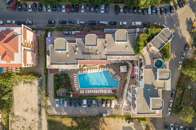 Top-down-luftbild von hoteldächern, straßen mit geparkten autos und schwimmbädern mit blauem wasser in urlaubsstadt nahe dem meer.