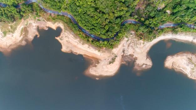 Top down von drohne luftbild des regenwaldes mit asphaltstraße um den damm