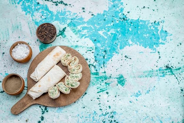 Top fernsicht leckere gemüsebrötchen ganz und in scheiben geschnitten mit gemüsefüllung und gewürzen auf hellblauem schreibtisch, essen mahlzeit brötchen gemüse