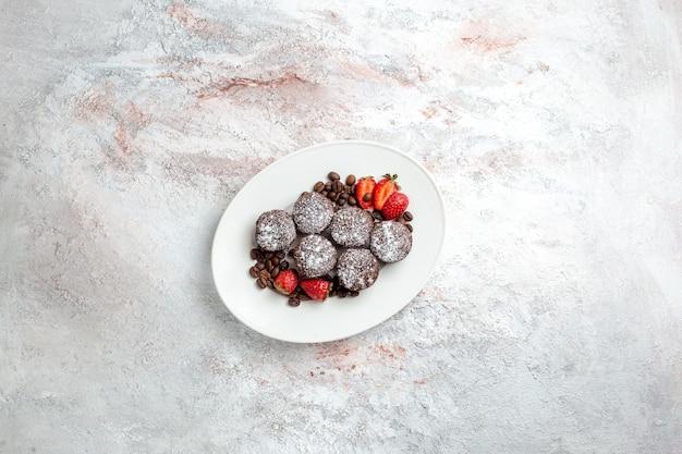 Top fernsicht leckere schokoladenkuchen mit erdbeeren und schokoladenstückchen auf weißer oberfläche kekskuchen backen zucker süßen kuchenplätzchen