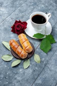 Top fernsicht tasse kaffee zusammen mit süßen leckeren armreifen auf grau