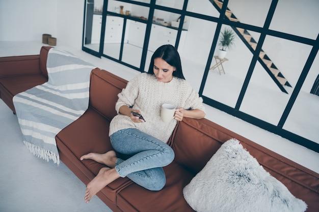 Top hoch über winkel konzentriert mädchen sitzen auf braunem leder diwan verwenden telefon lesen feednews beitrag kommentare halten tasse mit latte