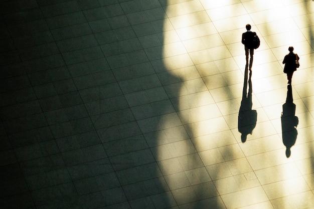 Top luftaufnahme des geschäftsmannes gehen in arbeitszeit am fußgänger. mit licht und schatten.