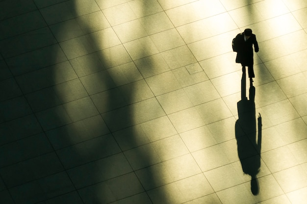 Top luftaufnahme des geschäftsmannes gehen und aktentasche in der arbeitszeit am fußgänger halten. mit licht und schatten.