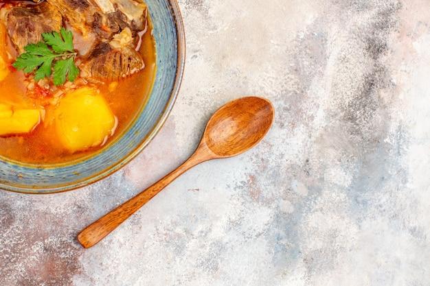 Top-nahansicht-bozbash-suppe ein holzlöffel auf nacktem hintergrund