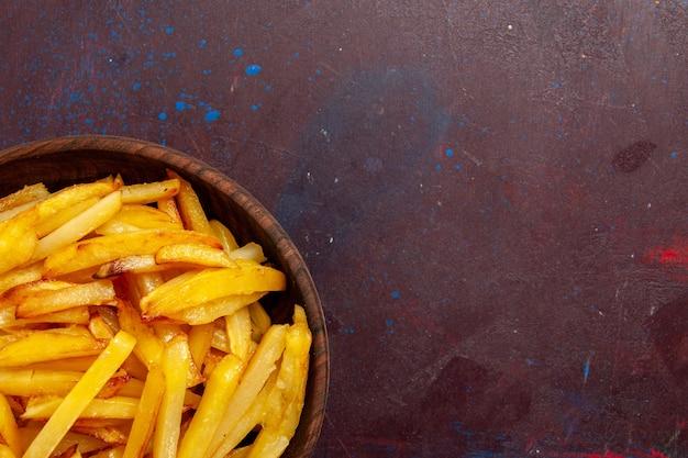 Top nahansicht bratkartoffeln leckere pommes frites in platte auf dunkler oberfläche lebensmittel mahlzeit abendessen gericht zutaten produkt kartoffel