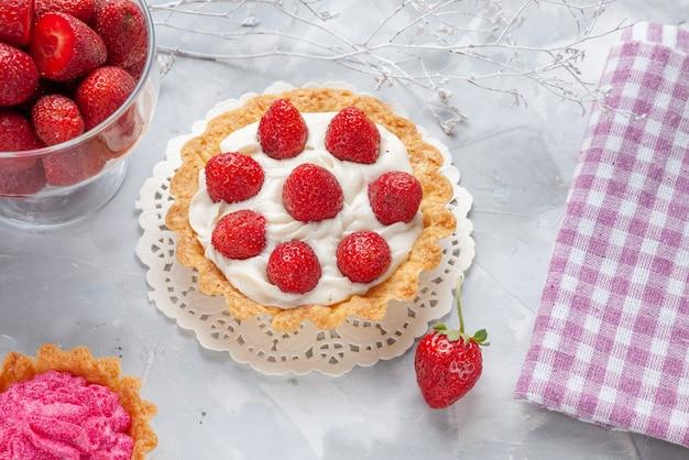 Top-nahansicht des kleinen kuchens mit sahne und frischem rosa sahnekuchen der roten erdbeeren auf weißem schreibtisch, kuchenfrucht-beeren-kekscreme