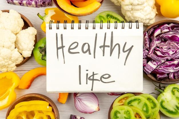 Top nahansicht gesundes leben geschrieben auf notebook geschnitten grüne tomaten geschnitten rotkohl geschnitten kürbis blumenkohl geschnitten paprika in schalen auf holzoberfläche