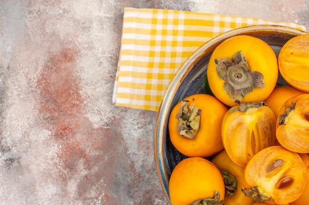 Top-nahansicht köstliche kaki in einem gelben küchentuch der schüssel auf nacktem hintergrund