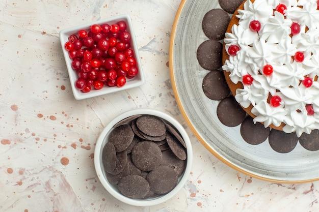 Top-nahansicht-kuchen mit gebäckcremebeeren und schokolade in schalen