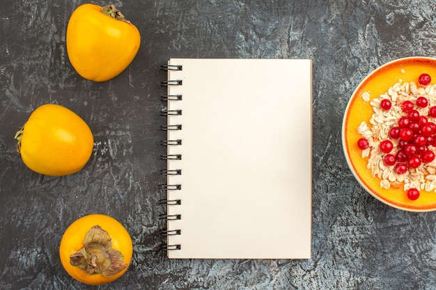 Top-nahansicht persimonen drei persimonen schüssel mit roten johannisbeeren notizbuch