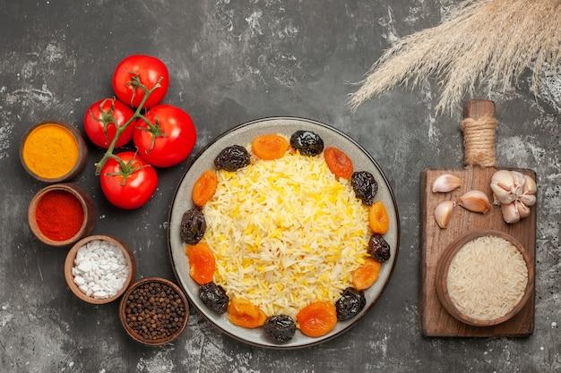 Top-nahansicht reisgewürze reis mit getrockneten früchten tomaten schüssel reis knoblauch auf dem brett