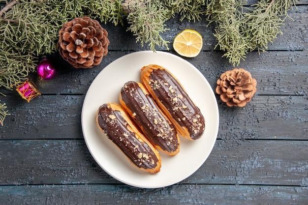 Top-nahansicht schokoladen-eclairs auf weißen ovalen tellerkegeln tannenbaum verlässt weihnachtsspielzeug zitronenscheibe auf dunklem holzboden mit kopierraum